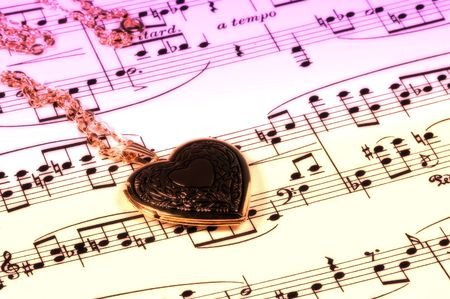 sheetmusic: Gold Heart Locket and Sheet Music With Color and Blur. Stock Photo