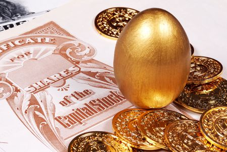 Gold Egg With Stock Certificate and Coins Stock Photo