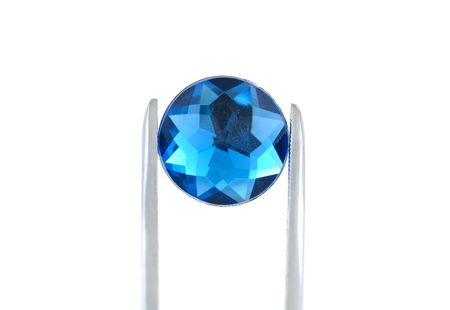 appraise: Photo of Tweezers Holding a Blue Gem