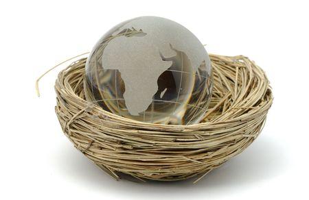 Glass Globe in a Nest - Global Population Concept Stockfoto