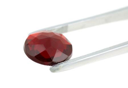 赤い宝石を保持しているピンセット