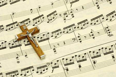 Crucifix on top of Sheet Music Stock Photo