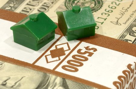 Miniature Houses on a Stack of Money Stock Photo