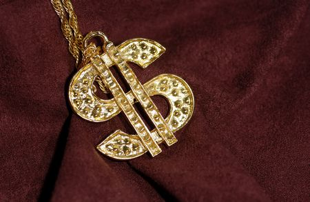 Photo of a Gold Dollar Symbol on a Burgundy Background - Bling / Wealth Stockfoto