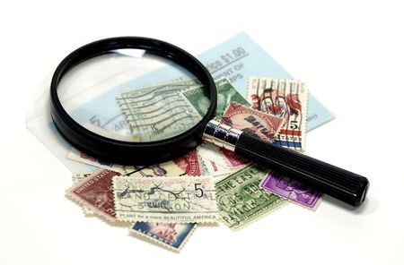 appraise: Photo of Postage Stamps and Magnifying Glass - Stamp Collecting Concept