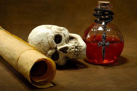 pocima: Foto de los pergaminos, del cráneo y de una botella de la poción - concepto mágico del encanto Foto de archivo