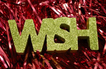 Photo of Red Tinsel and The Word Wish With Green Glitter  -  Christmas Related Stock Photo