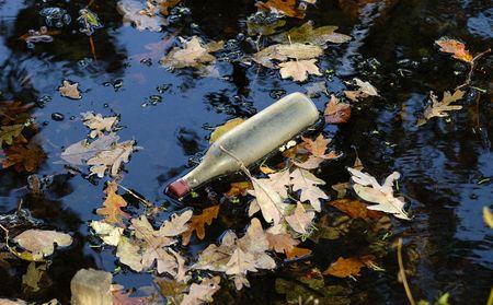 Foto de una botella flotante en el agua turbia  Foto de archivo - 1976505