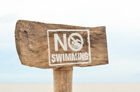 no swimming sign: No swimming sign at the beach photo