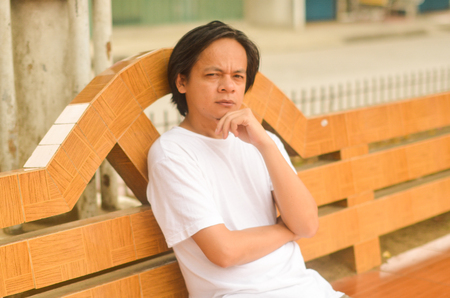 Asian man thinking with hand on chin photo Stock Photo