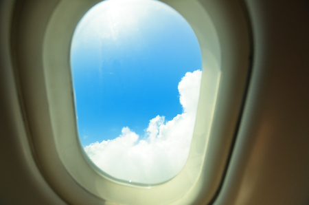 Airplane window showing blue sky and white clouds