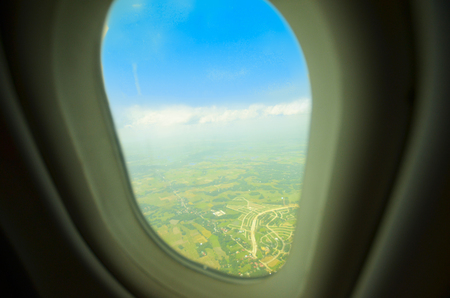Airplane window showing land and blue sky