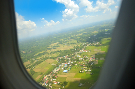 Airplane window showing land and white clouds Imagens