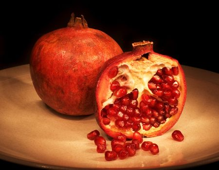 Pomegranate sliced on plate with dark background