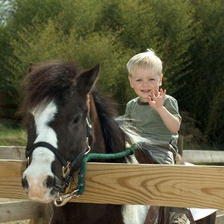 Little boy riding on poney photo