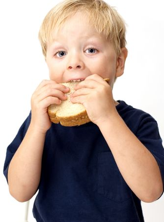 Boy taking a big bite of its peanut butter sandwich photo