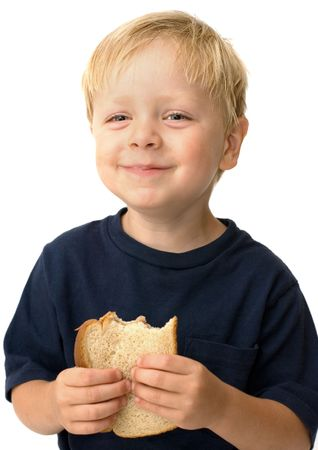 Little boy showing satisfaction while eating a peanut butter sandwich photo