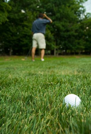 Camera zooming on golf ball with puzzled golfer in the back