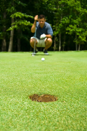 aligning: Golfer crouching to evaluate the inclination level of a putting green.  Focus on the hole.  Stock Photo