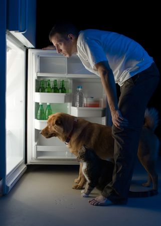 refrigerator with food: Man and his pets looking for food in the refrigerator Stock Photo