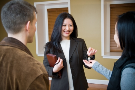 Realtor handling house key to new happy home owner Stock Photo