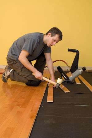 madeira de lei: Man installing tongue and groove hardwood floor.