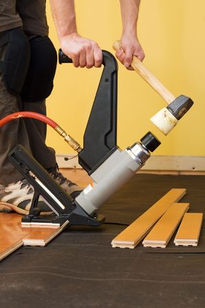 hardwood: Man installing tongue and groove hardwood floor.
