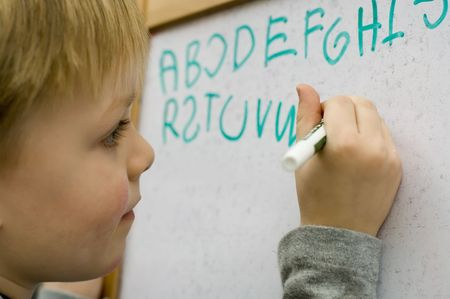 Little boy learning to write alphabet on white board photo