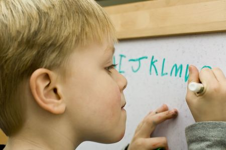 4 years old boy learning to write alphabet on white board photo