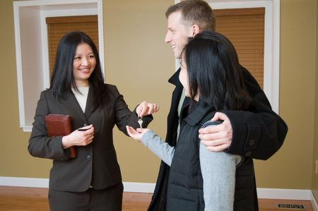 sales agent: Woman offering key to house to couple