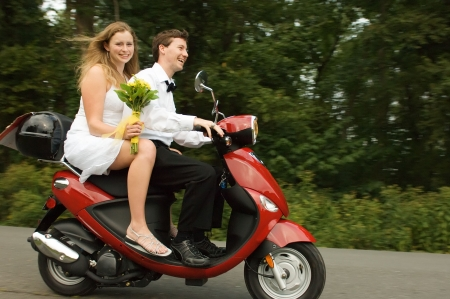 Happy young married couple on a scooter