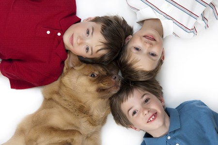 Three happy boys posing with their dog