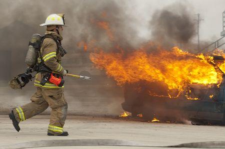 coche de bomberos: Bombero corriendo hacia el veh�culo en llamas. Este fue un ejercicio de simulacro.
