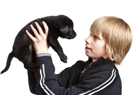 holding close: Teenager holding a black puppy dog. Image on white background