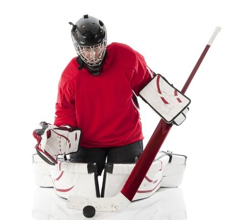 hockey sobre hielo: Guardameta de hockey sobre hielo bloqueando un puck en estilo mariposa. Foto sobre fondo blanco