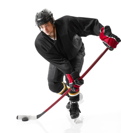 hockey puck: Ice hockey player handling puck and skating forward, white background