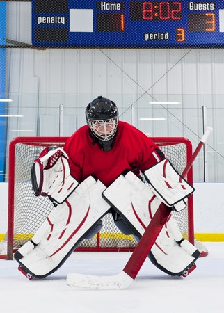 ice rink: Ice hockey goalie in front of his net. Picture taken on ice rink. Stock Photo