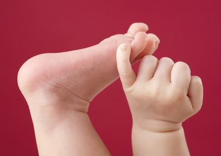 baby foot: Close-up en pie de beb� y mano sobre fondo rojo