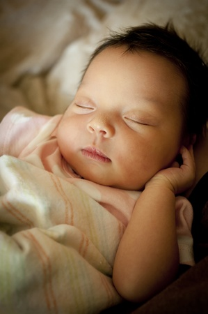 Newborn baby wrapped in blanket sleeping on her back. Stock Photo