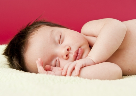 Newborn baby sleeping on its side photo
