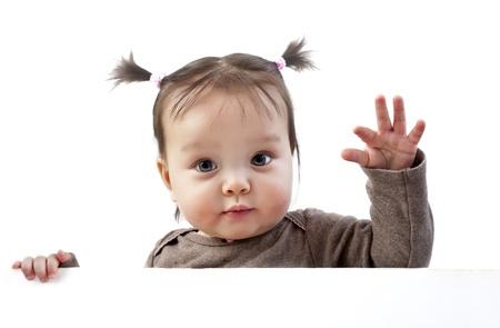 fondo para bebe: Ni�a con coletas agitando la mano por encima de la bandera blanca Foto de archivo