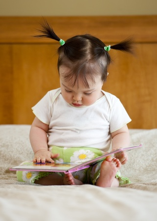 page down: Baby girl sitting with opened book