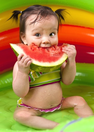 Baby girl eating watermelon in wading pool Stock Photo