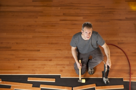 tongue and groove: Man installing planks of hardwood floor