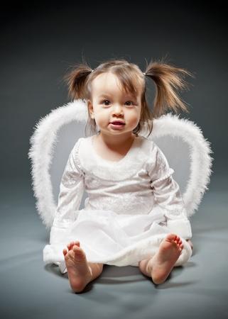 여자 아기가 앉아 천사 같이 옷을 입고