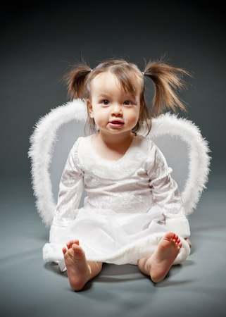 asian angel: Baby girl sitting and dressed as an angel