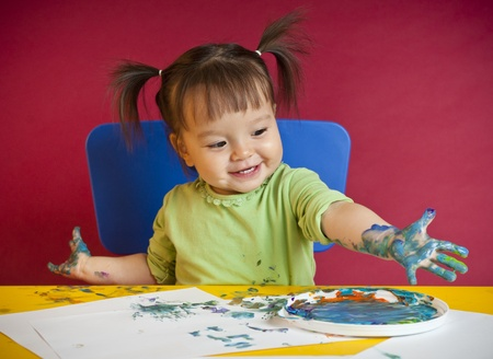 Little happy girl discovering finger painting Stock Photo