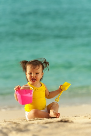 One year old baby girl playing in the sand on the beach  Ocean as background photo