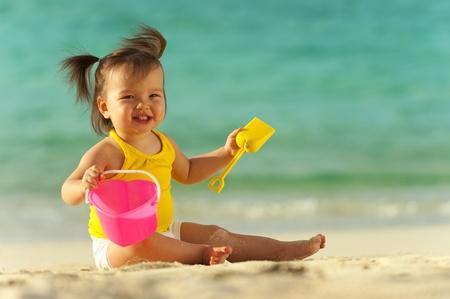 klein meisje op strand: Baby meisje spelen in het zand op het strand Oceaan als achtergrond Stockfoto