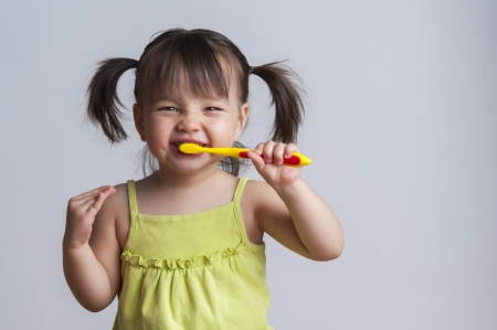 Toddler smiling while brushing her teeth photo